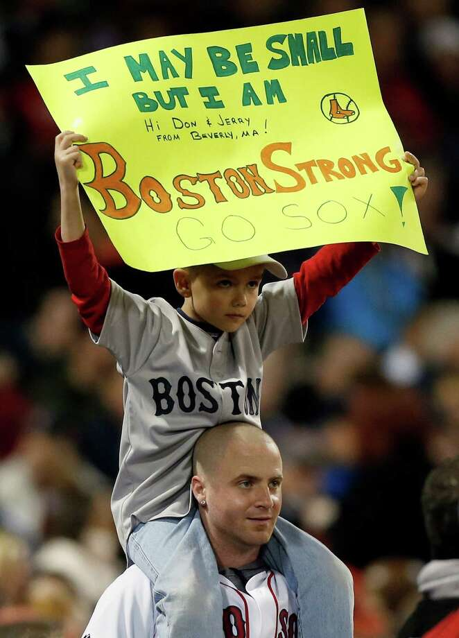 A young fan holds a Boston Strong sign in the sixth inning of a baseball game against the Houston Astros in Boston, Saturday, April 27, 2013. (AP Photo/Michael Dwyer) Photo: Michael Dwyer, Associated Press / AP