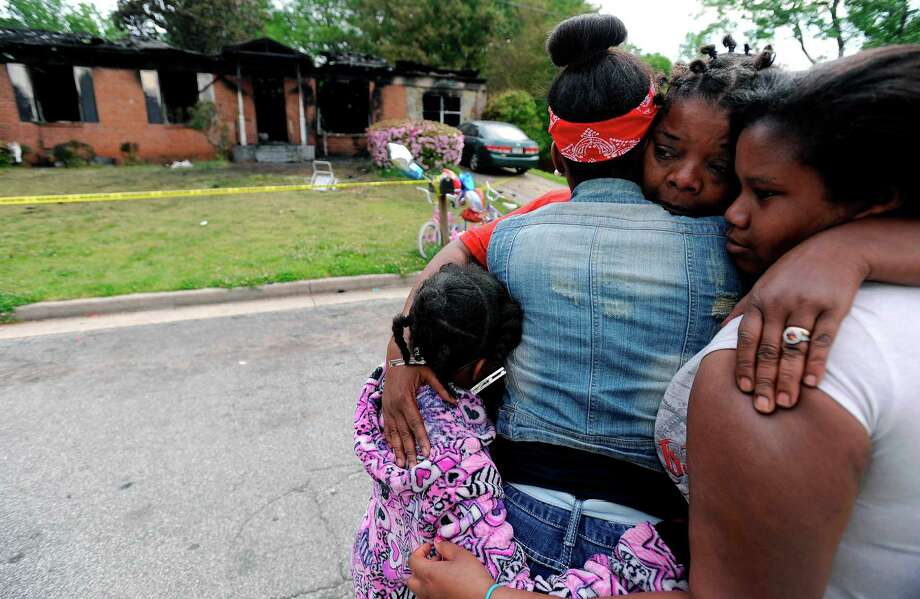 Sisters Brandy McCrary, left, and Breona Montgomery, who are cousins of the five fatal house fire victims, hug neighbors Bonita Beasley, center, and Jennifer Moss, right, in Newnan, Ga., Saturday, April 27, 2013.  The fire killed Alonna T. McCrary, 27, as well as her 5-year-old daughter Eriel McCrary and 2-year-old daughter Nikia White. Two other children, Messiah White, 3, and McKenzie Florence, 2, also died. (AP Photo/David Tulis) Photo: David Tulis, Associated Press / FR170493 AP