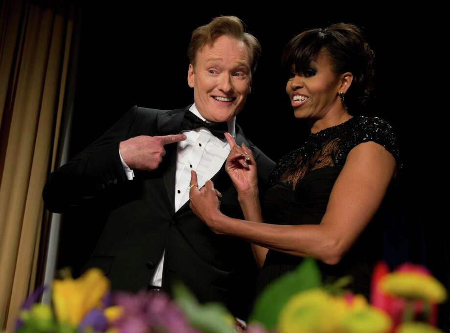 First lady Michelle Obama and late-night television host and comedian Conan O'Brien gesture to his tie at the White House Correspondents' Association Dinner at the Washington Hilton Hotel, Saturday, April 27, 2013, in Washington.  (AP Photo/Carolyn Kaster) Photo: Carolyn Kaster, Associated Press / AP