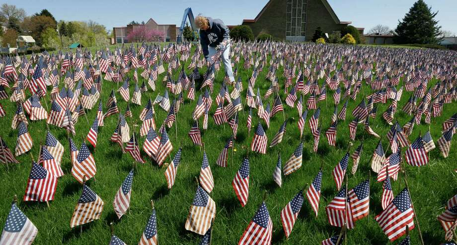 "Nancy Nogacek, a member of the Military Care Committee at their church, helps tend to the some of the American flags on display as part of their ""Field of Flags"" in front of the Memorial Park Church, Saturday, April 27, 2013, in McCandless, Pa. The display of more than 6,000 flags is to commemorate veterans killed in Iraq and Afghanistan. (AP Photo/Keith Srakocic) Photo: Keith Srakocic, Associated Press / AP"