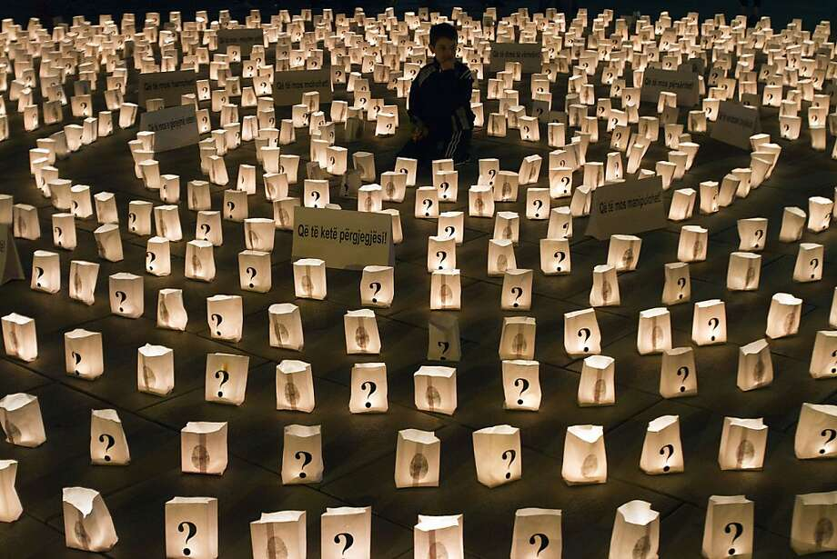 A Kosovo boy sits in the middle of a circle of lit candles to commemorate those who went missing during 1998-99 Kosovo war, in Pristina, Kosovo, late Friday, Apr 26, 2013. International agencies estimated over a thousand people remain missing in Kosovo.  Photo: Visar Kryeziu, Associated Press
