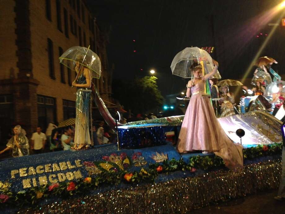 Fiesta queens hold clear umbrellas as rain starts to fall on the Fiesta Flambeau Parade on Saturday night, April 27, 2013.