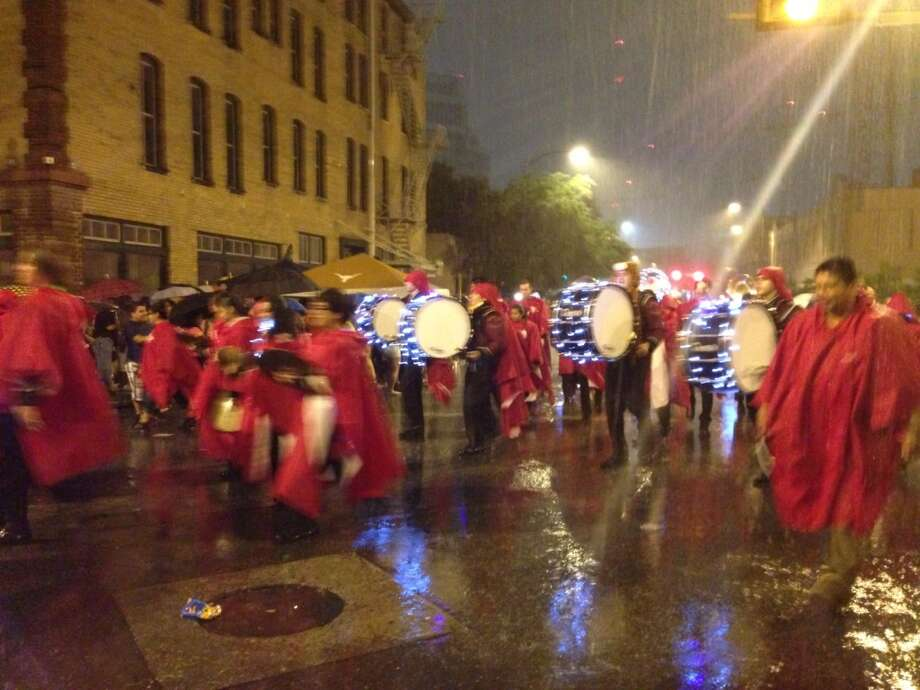 A marching band braves the rain at the Fiesta Flambeau Parade on Saturday night, April 27, 2013.