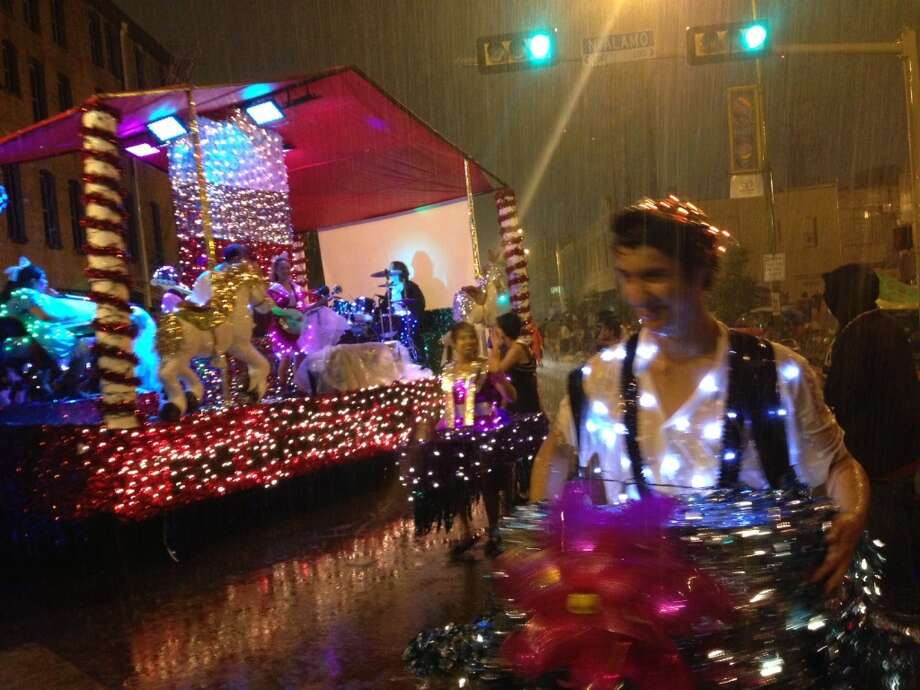 A float by the San Antonio School for Inquiry and Creativity braves the rain at the Fiesta Flambeau Parade on Saturday night, April 27, 2013.