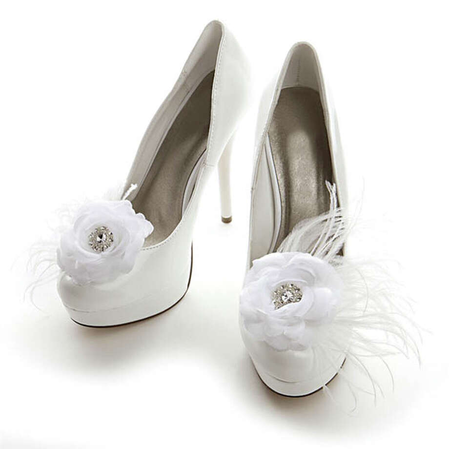 Put a Clip on It Want to add a little flair to your footwear? These satin rose shoe clips fit easily onto the fronts or backs of your bridal shoes. Made by Mariell, these white organza and satin rose clips are nestled in 2 and a half inches of ostrich feather spray. The 3-inch-round flowers have glistening crystal centers. Find  a retailer through