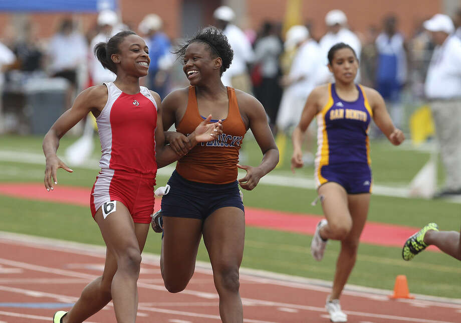 Winner Talajah Murrell of Judson (left) and runner-up Yasmyn Richards of Madison celebrate after qualifying for the Class 5A state meet in the 100-meter dash Saturday afternoon at Heroes Stadium. Photo: Photos By Kin Man Hui / San Antonio Express-News
