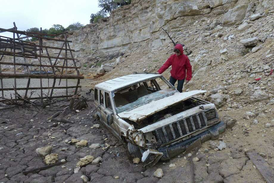 Karen Ripley, who lives near Medina Lake, checks out a Jeep that receding waters left exposed at Elm Cove. Photo: Billy Calzada / San Antonio Express-News
