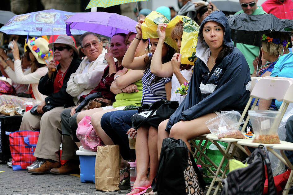Rain threatens spectators on Commerce Street as the Battle of Flowers Parade moves through the downtown area  on  April 26 2013.