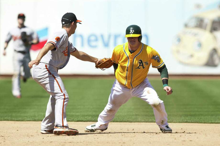 The Orioles' J.J. Hardy (left) tags out the Athletics' Josh Donaldson after a pick-off play in the sixth. Photo: Jason O. Watson / Getty Images