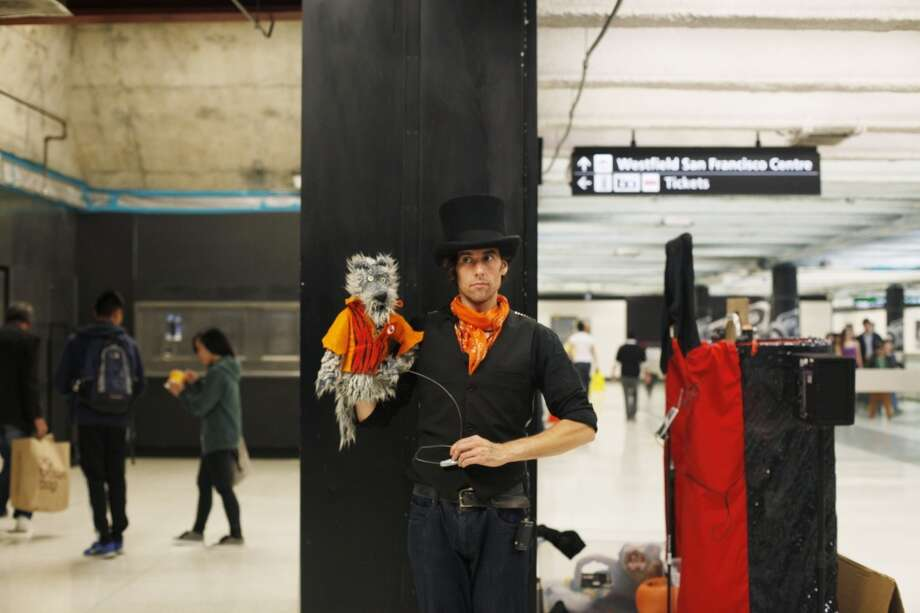 Puppeteer Nick Jones performs holds his favorite puppet Wolfie, during a break in performing at the Powell Street BART station in San Francisco.