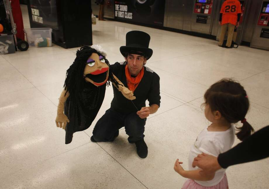 Holding a character he calls Mary Jane Lane, puppeteer Nick Jones brings his show closer to a curious girl in the Powell Street BART station in San Francisco.