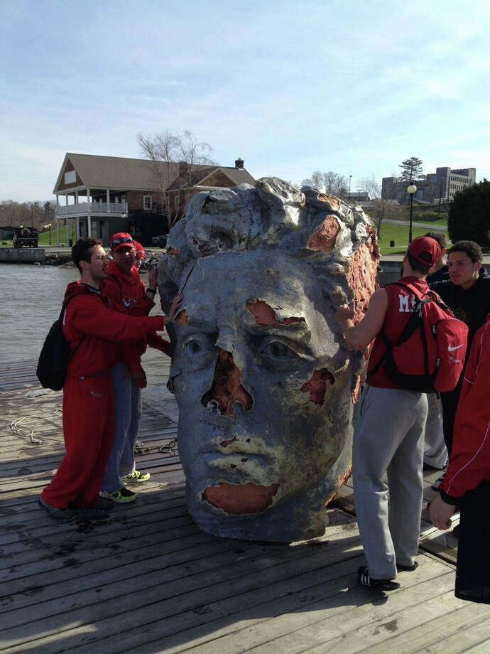 In this April 22, 2013 handout photo provided by Tyler Sawyer of the Marist College crew team , members of the team stand by a giant head made of Styrofoam and fiberglass found floating in the Hudson River in Poughkeepsie, N.Y. Officials at the college say the team was practicing earlier this week when the coach spotted a large object floating near the river's west bank. He hooked a rope to it and towed it to the team's dock on the east bank. Photo: AP