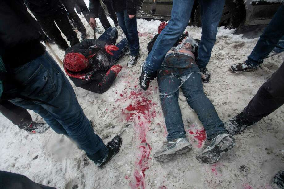 In this photo taken on Friday, March 15, 2013, members of a pro-Kremlin youth group douse with red paint two tied-up pushers of spice, a synthetic drug, in Moscow, Russia. Russian officials and anti-drugs campaigners say that spice has become one of the most dangerous drugs widely available to youngsters and almost impossible to ban because of the constantly changing chemical ingredients. Photo: AP