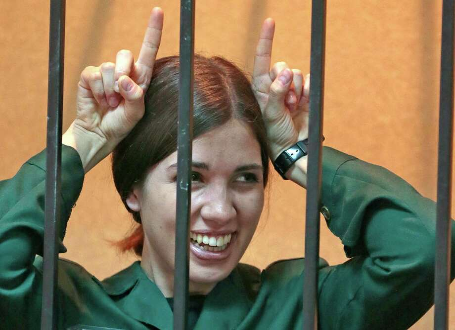 Nadezhda Tolokonnikova, a member of the feminist punk band, Pussy Riot, gestures at a district court from behind bars in Zubova Polyana 440 km southeast of Moscow in Russia's province of Mordovia, Friday, April 26, 2013. Tolokonnikova was denied parole on Friday from the penal colony where she is serving a two-year sentence on charges of hooliganism motivated by religious hatred.