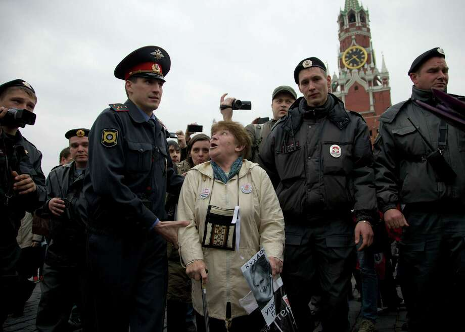 Russian police officers detain a demonstrator during an action in support of opposition activists arrested in a massive anti-president Putin rally in last May, in Red Square, with the Kremlin's Spassky Tower in the background, in Moscow, Saturday, April 27, 2013. Photo: AP