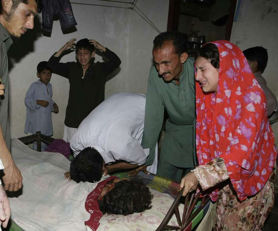 People mourn the death of their family member in a blast in Karachi, Pakistan Friday, April 26, 2013.  A bomb planted near the office of a political party threatened by the Taliban has killed many people in southern Pakistan, police said. Photo: AP