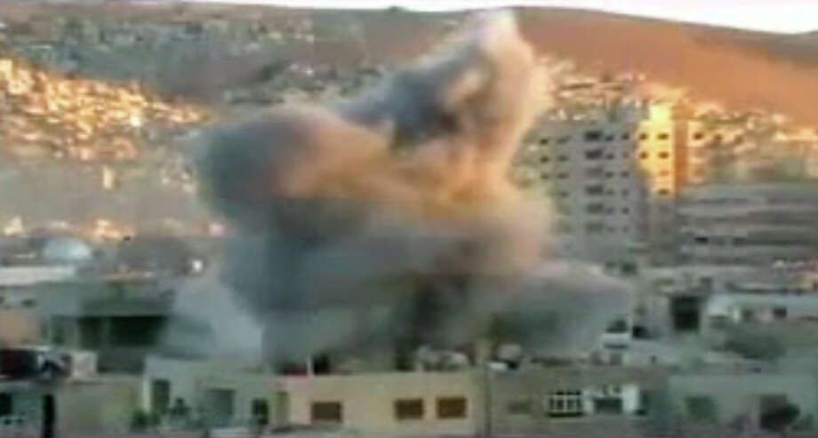 This image taken from video obtained from Ugarit, which has been authenticated based on its contents and other AP reporting, shows an explosion during heavy fighting between rebels and Syrian government forces in the Barzeh district of Damascus, Syria, Friday, April 26, 2013. On the streets of Damascus, the two-year old conflict dragged on Friday, with government troops pushing into two northern neighborhoods, triggering heavy fighting with rebels as they tried to advance under air and artillery support, activists said. The Britain-based Syrian Observatory for Human Rights said the fighting between rebels and soldiers backed by pro-government militiamen was concentrated in the Jobar and Barzeh areas. Photo: AP