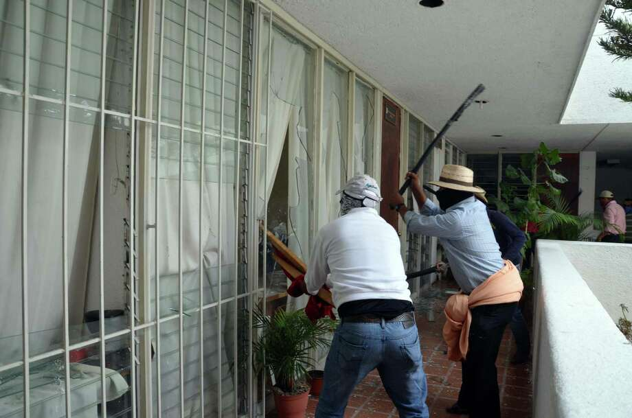Protesting against President Pena Nieto's education reform project, teachers break windows during an attack on the Revolutionary Institutional Party, PRI, regional offices, causing significant damage, in Chilpancingo, Mexico, Wednesday April 24, 2013. Thousands of elementary and high-school teachers in Guerrero, one of the country's poorest and worst-educated states, walked off their jobs more than a month ago, turning away hundreds of thousands of children from their classrooms and since launched an increasingly disruptive string of protests. Photo: AP