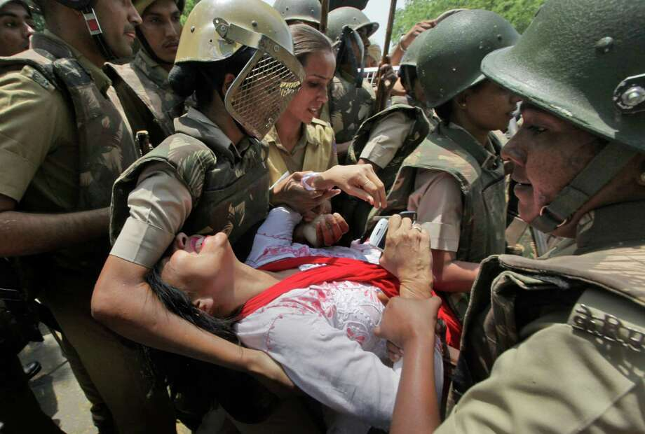 Indian police officers detain a protestor during a protest outside the Parliament in New Delhi, India, Monday, April 22, 2013. A second suspect was arrested Monday in the rape of a 5-year-old girl who New Delhi police say was left for dead in a locked room, a case that has brought a new wave of protests against how Indian authorities handle sex crimes. Photo: AP