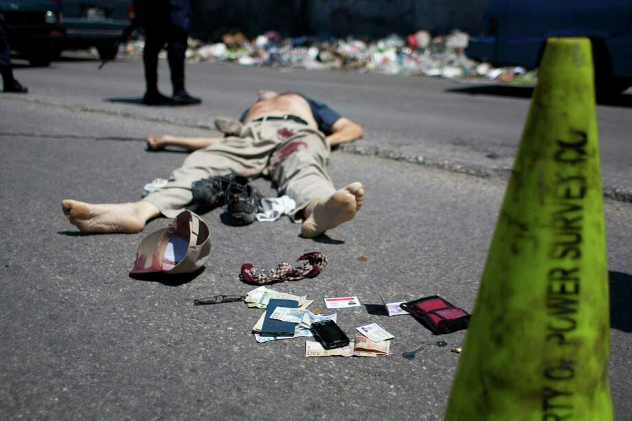 Cash and personal belongings that were placed there by police lay next to slain Canadian priest Richard E. Joyal in the Delmas district of Port-au-Prince, Haiti, Thursday, April 25, 2013. Police inspector Aladin Jean-Louis says that the 62-year-old Joyal had just withdrawn (Canadian) $1,000 from a bank when two men on a motorcycle approached and grabbed a bag he was carrying, and the passenger shot him three times in the back. Authorities later found the $1,000 in Joyal's wallet in his pocket and placed it at his feet. The contents of Joyal's billfold included a driver's license showing he was from Quebec. Another identification card showed he was a priest who worked as an administrator for a Canadian congregation in the Delmas district of Port-au-Prince. Photo: AP