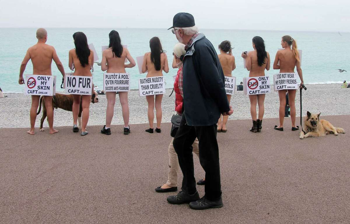 Tourists pass by members of the French branch of the international anti-fur group
