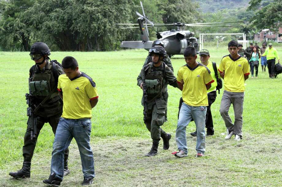 Alleged rebels from Revolutionary Armed Forces of Colombia, or FARC, are escorted by Colombian Police agents in Cali, Colombia, Friday, April 26, 2013. Colombia's President Juan Manuel Santos announced on Friday that police captured 17 rebels in Puerto Tejada in the Cauca State. Photo: AP