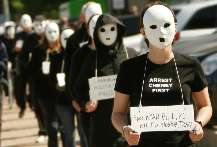 Protesters walk with masks on in Dallas near the dedication of the opening of the George W. Bush Presidential Center in Dallas, on Thursday, April 25, 2013. Police arrested at least three people during the protest march. Photo: AP