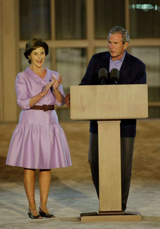 Former president George W. Bush, right, with former first lady Laura Bush, addresses the audience during the lighting of Freedom Hall ceremony at the George W. Bush Presidential Center Thursday, April 25, 2013, in Dallas. (AP Photo/David J. Phillip) Photo: AP
