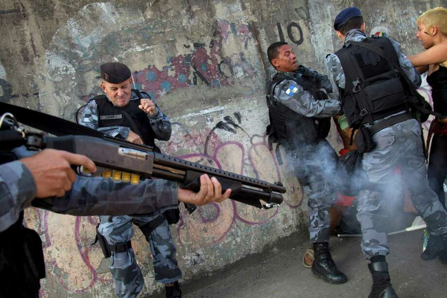 Activists clash with Brazilian police as another officer fires tear gas at the activists protesting the privatization of the Maracana stadium and planned demolition of the indigenous museum located next to the stadium, in Rio de Janeiro, Brazil, Friday, April 26, 2013. Protestors are against the privatization of the stadium because it will lead to the demolition of the museum and a public school. After a series of delays, criticisms and protests, the iconic Maracana will reopen Saturday to host a friendly match between teams put together by former football stars Ronaldo and Bebeto - in a test event ahead of the Confederations Cup in June. Photo: AP