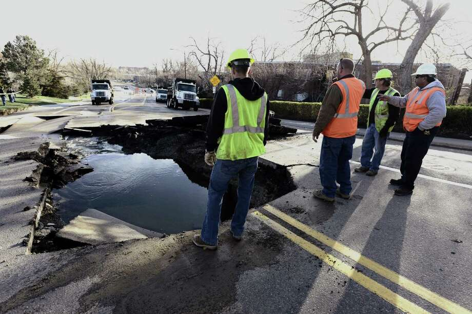 Workers look over a sinkhole at Stadium Drive and Folsom in Boulder, Colo., near the football stadium on the University of Colorado Boulder Campus Thursday, April 25, 2013. The large sinkhole, caused by a water-main break, is causing major problems in Boulder. Nearby apartment buildings do not have water and traffic is snarled. (AP Photo/The Daily Camera, Paul Aiken) Photo: AP
