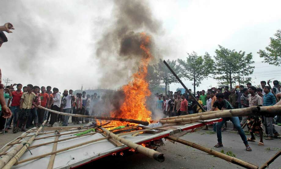 Bangladeshi garment workers set fire to a billboard during a protest against the collapse of an eight-story building that housed several garment factories and poor working conditions of the employees, in Dhaka, Bangladesh, Saturday, April 27, 2013. Police in Bangladesh took into custody five people in connection with the collapse of a shoddily-constructed building that collapsed this week, as rescue workers pulled out 19 survivors out of the rubble on Saturday and vowed to continue as long as necessary to find others despite fading hopes. Photo: AP