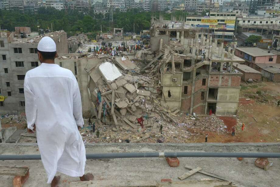A man watches while rescue workers search for survivors at a garment factory building that collapsed Wednesday in Savar, near Dhaka, Bangladesh, Saturday, April 27, 2013. Police in Bangladesh took five people into custody in connection with the collapse of a shoddily-constructed building this week, as rescue workers pulled 19 survivors out of the rubble on Saturday and vowed to continue as long as necessary to find others despite fading hopes. Photo: AP