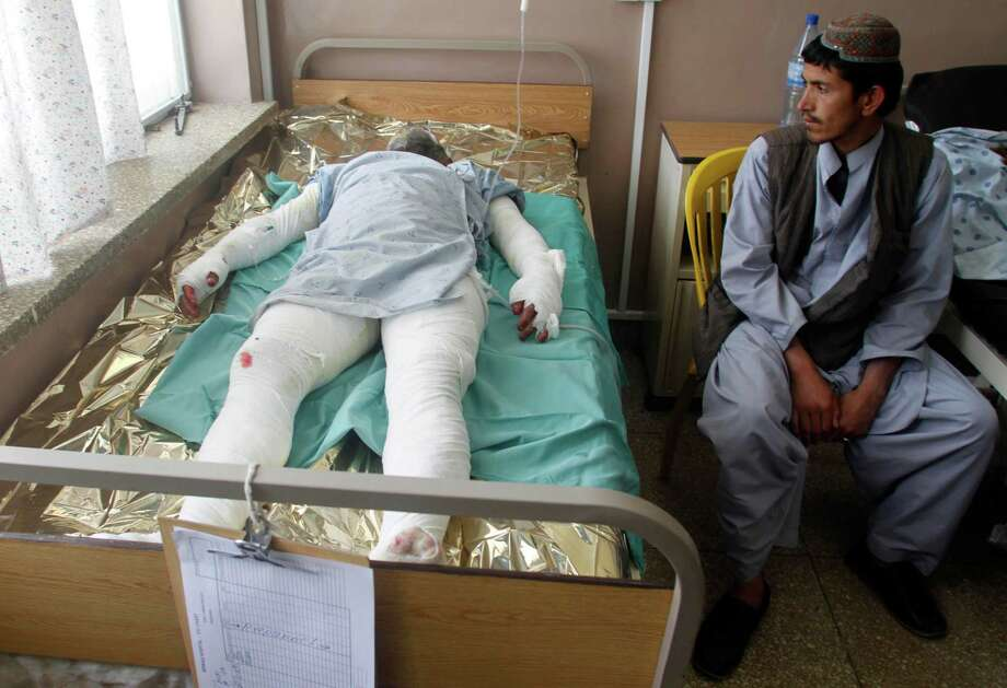 An Afghan man visits a wounded relative in the hospital in Kandahar, Afghanistan, Friday, April 26, 2013 after a bus collided with the wreckage of a truck that was attacked by Taliban insurgents in Maiwand district, on the highway between Kandahar and Helmand, Afghanistan,Friday, April 26, 2013. Scores of people aboard the bus were killed in the fiery crash, officials said. Photo: AP
