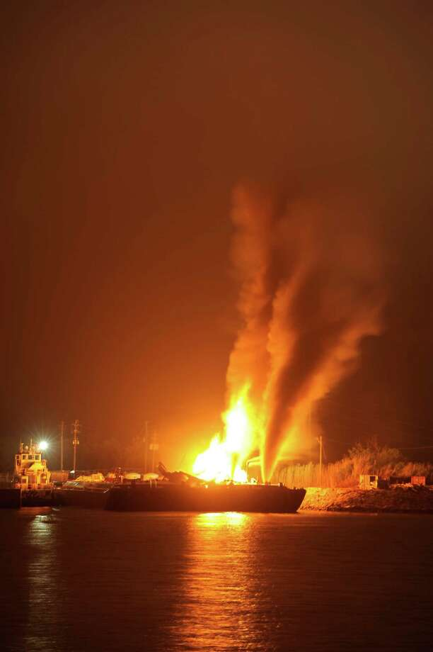 Fire burns aboard two fuel barges Wednesday April 24, 2013 along Mobile River after explosions sent three workers to the hospital. Fire officials have pulled units back from fighting the fire due to the explosions and no immediate threat to lives. Photo: AP