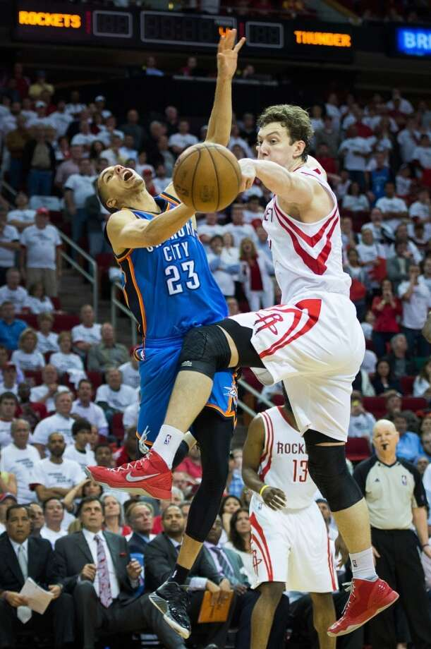 Rockets center Omer Asik knocks the ball away from Thunder guard Kevin Martin. Photo: Smiley N. Pool, Houston Chronicle
