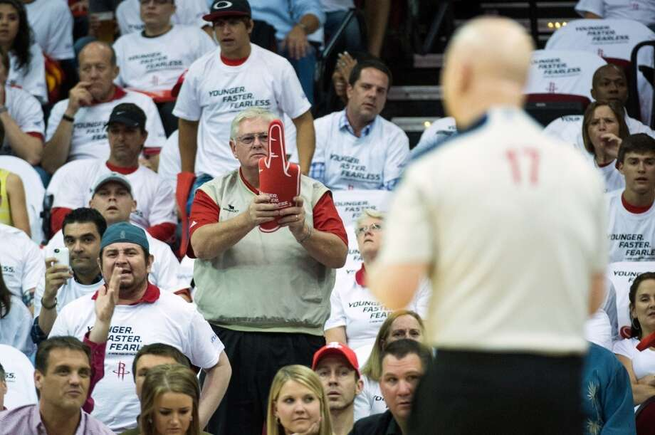 A Rockets fan twists a foam 3-point hand into an obscene gesture toward referee Joe Crawford during the first half. Photo: Smiley N. Pool, Houston Chronicle