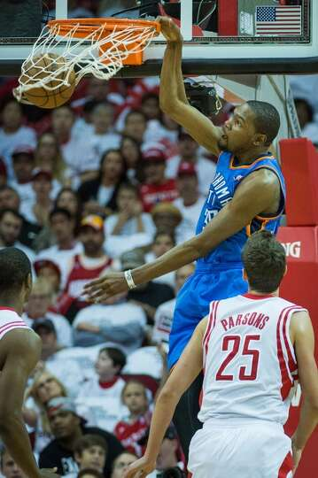 Thunder forward Kevin Durant dunks the ball as Rockets small forward Chandler Parsons looks on durin