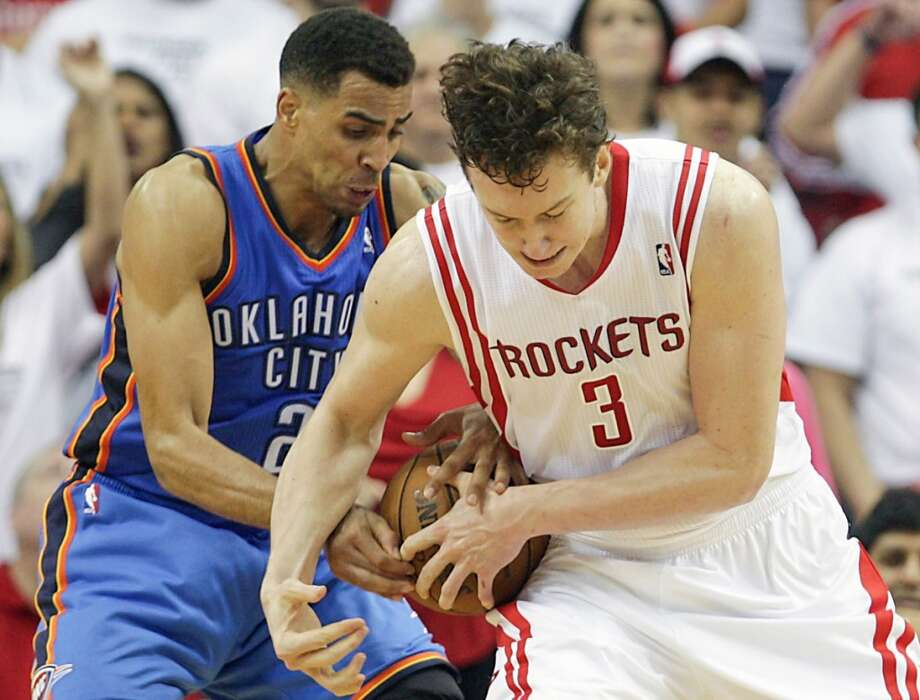 Thunder shooting guard Thabo Sefolosha left, and the Rockets center Omer Asik right, wrestle for the ball during the second half. Photo: James Nielsen, Houston Chronicle