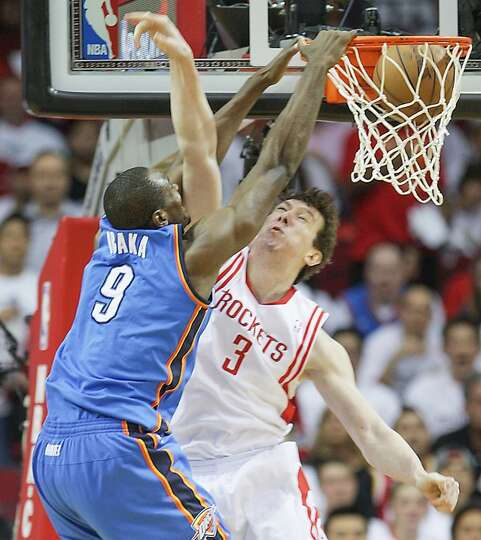 Thunder power forward Serge Ibaka slam dunks the ball over the Rockets center Omer Asik.