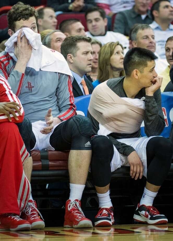 Rockets point guard Jeremy Lin sits on the bench with ice on his chest as center Omer Asik wipes his face with a towel during the first half. Photo: Smiley N. Pool, Houston Chronicle