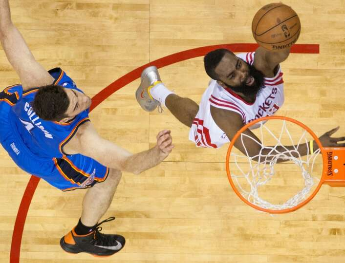 Rockets shooting guard James Harden goes up for a layup past Thunder power forward Nick Collison dur