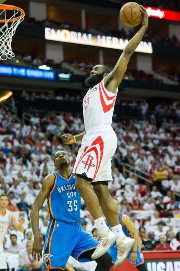 Rockets guard James Harden goes up for a dunk as Thunder forward Kevin Durant looks on during the fi