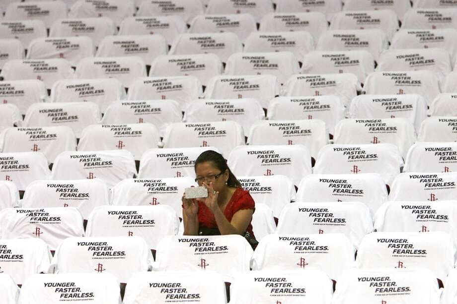 Gemma Croley takes a photograph in the t-shirt covered seats prior to the game. Photo: James Nielsen, Houston Chronicle