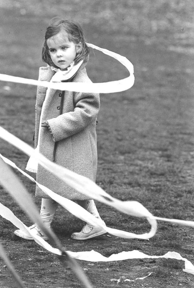 Three-year-old Catherine Hughes pulls a crepe paper strand off the maypole during the 1988 May Day celebration at the Stamford Museum and Nature Center. Photo: File