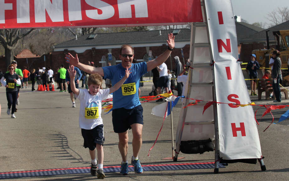 Father and son, Ryan, 9, and Dave Keenan, of Westport, finish the 5K  of the Westport Young Women's League's 2013 35th annual Minute Man race at Compo Beach in Westport, CT on Sunday, April 28, 2013. Photo: BK Angeletti, B.K. Angeletti / Connecticut Post freelance B.K. Angeletti