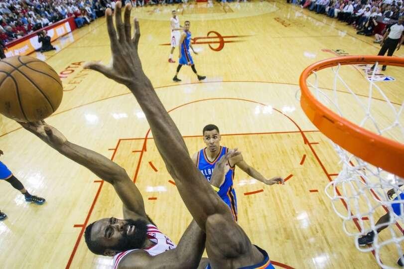 Rockets guard James Harden puts up a shot as Thunder power forward Serge Ibaka defends.