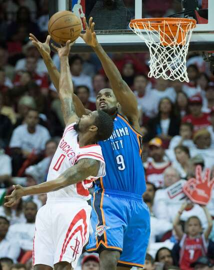 Rockets point guard Aaron Brooks knocks the ball away from Serge Ibaka.