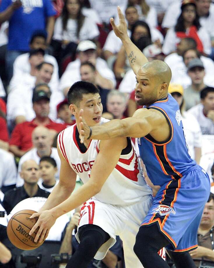Rockets point guard Jeremy Lin passes the ball past the Thunder point guard Derek Fisher. Photo: James Nielsen, Houston Chronicle