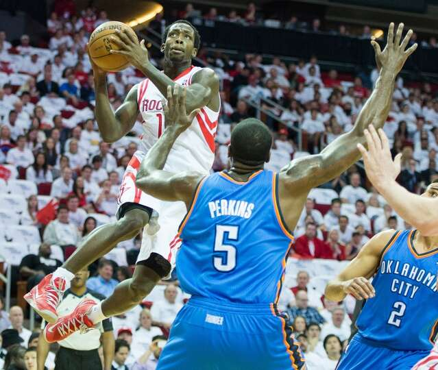 Rockets point guard Patrick Beverley drives to the basket as Thunder center Kendrick Perkins defends