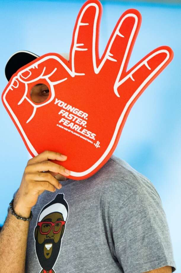 A Rockets fan checks out a giveaway foam hand as he arrives for Game 3. Photo: Houston Chronicle
